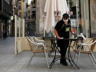 Una camarera con mascarilla limpia la terraza de un bar en Lleida
