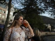 Una mujer bebe alcohol en la calle.
