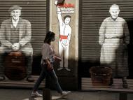 Una mujer con mascarilla pasa ante un bar cerrado en Madrid