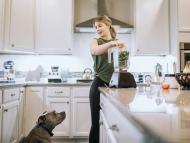 Una mujer con un perro en la cocina haciendo un batido de espinacas.