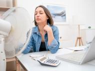 Mujer con ventilador en la oficina.