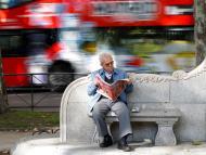 Pensionista lee un periódico en Madrid