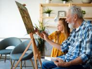Un señor mayor dibuja en un lienzo.