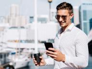 Un hombre rico mira su móvil en un club náutico.