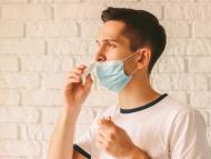 Joven con aerosol nasal y mascarilla.
