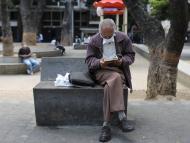 Un jubilado lee un libro en parque con una mascarilla puesta