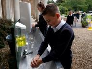 Alumno británico lavándose las manos