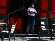 Un camarero con mascarilla a las puertas de un bar en Madrid, España.
