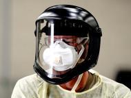 Una persona se protege con un casco y una mascarilla durante la pandemia del coronavirus