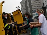 Un trabajador de Correos entrega comida a domiciio a trabajadores del hospital madrileño de La Paz
