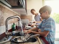 Niños fregando los platos.