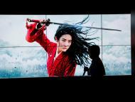 Una persona pasa por delante de una pantalla con Mulan en Pekín, última película de Disney estrenada en Disney Plus.
