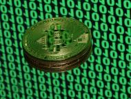 A token of the virtual currency Bitcoin is seen placed on a monitor that displays binary digits in this illustration picture, December 8, 2017. REUTERS/Dado Ruvic/Illustration