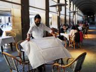 Camarera con mascarilla prepara una mesa en una terraza, en Barcelona.