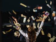 Una mujer con los brazos en alto, mientras billetes de dinero vuelan sobre ella.