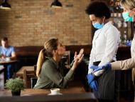 Una mujer discute con los camareros o encargados en un bar.