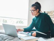 mujer con el ordenador en la cama
