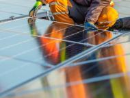 Un operario instala una placa fotovoltaica