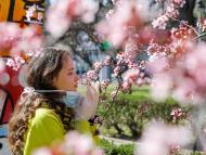 Una chica se quita la mascarilla para oler las flores