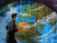 Un hombre pasea delante de un mural en medio de la pandemia del coronavirus