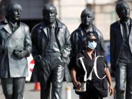 Una mujer camina delante de una estatua de los Beatles en Liverpool