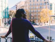Una mujer mira a la calle desde su ventana.