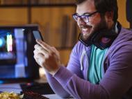 Un hombre sonriendo mirando su móvil