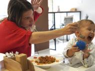 Una madre intenta dar de comer a su hijo.