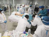 Varias personas atienden a un paciente de COVID en el Hospital Isabel Zendal de Madrid.