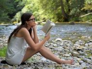 Una chica lee un libro en la orilla del río.