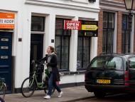 Una mujer con bicicleta pasa ante varias viviendas en venta en el centro de Amsterdam