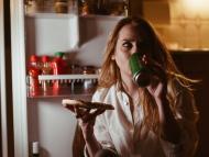 mujer comiendo pizza por la noche beber