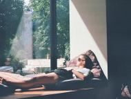 mujer mirando por la ventana, relajada