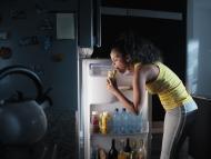 Una mujer saca un bocadillo de la nevera por la noche.