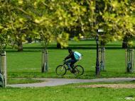Un repartidor de Deliveroo circula por un parque en Londres