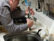 Un fontanero trata de arreglar un grifo.