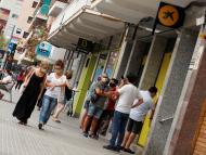 La gente pasea por la calle de los bancos.