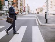 Un hombre camina por la calle mirando el móvil