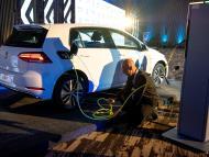Un hombre carga un coche eléctrico
