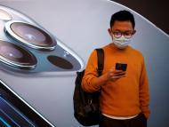 Un hombre delante de un cartel con el iPhone 12 de fondo