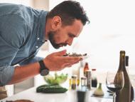 Un hombre oliendo un plato de comida