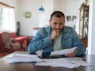 Un hombre revisa facturas, documentos.