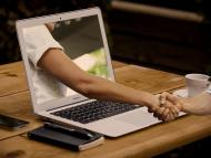 Una mano sale del ordenador y choca con la mano del usuario que está fuera.
