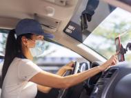 Una mujer busca una dirección en el móvil dentro del coche.