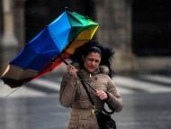 Una mujer se cubre con un paraguas