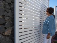Una mujer observa una vivienda con jardín desde la verja en Canarias