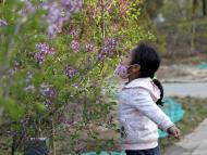niña huele flores con mascarilla