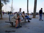 Personas sentadas en un banco en la playa con mascarilla.