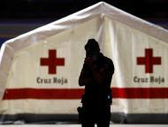 Un policía custodia una carpa de la Cruz Roja con cuerpos de inmigrantes muertos encontrados en un barco.