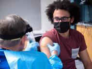Richard Biggs, estudiante de biología de la Universidad de Colorado Boulder, recibe su primera dosis de la vacuna de Moderna.